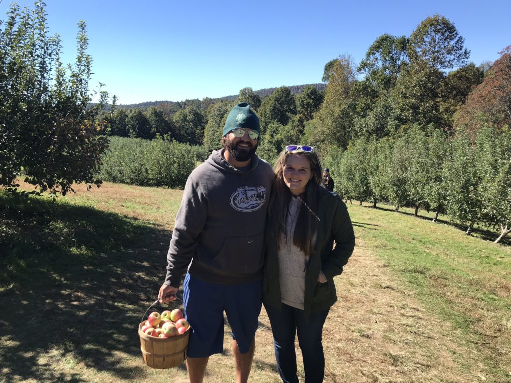 couple smiling at apple orchard